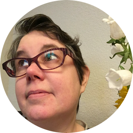 Dinah posing next to some flowers. Her short hair—needing a haircut due to quarantimes—has begun to form a dramatic curl like a wave on the top of her head. She is wearing glasses and looks bemused.