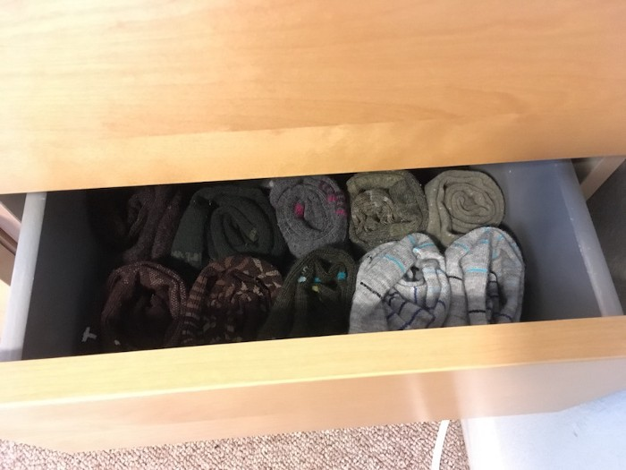 A drawer holding rows of neatly rolled socks, which are held in place in a hidden paper tray.