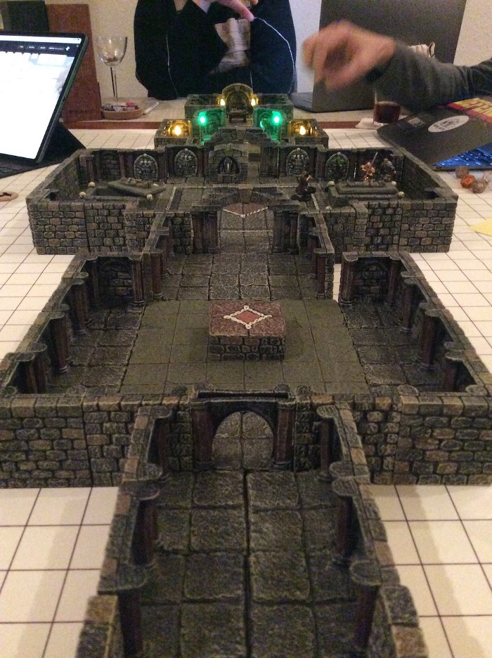 A view down a table with a multi-room tomb laid out with 3D terrain tiles resting on an erasable gridded mat. Beyond the entry hall and first room, through an archway, miniature figures can be seen in a room with an open sepulcher gathered around a closed one. In the background is a stone shrine with a dagger on it which has moved aside to reveal a chamber beyond lit by green and gold lights.