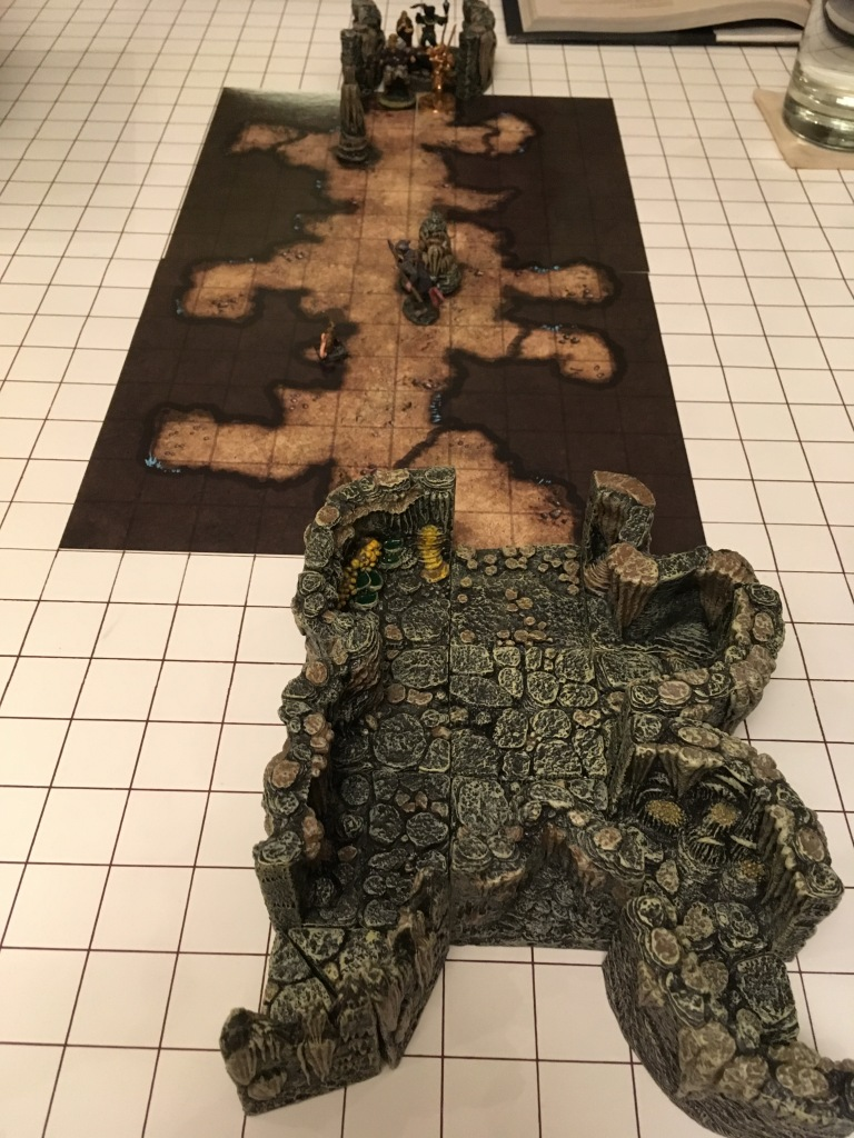 "An erasable 1"" grid mat is on  table, sitting atop it in the center are color map cards with a view of above of a cave area. At the top and bottom edge, connecting to the cave map, are pieces of 3D terrain which extend the map. Miniature figures of stalagmites and characters are placed on the map."