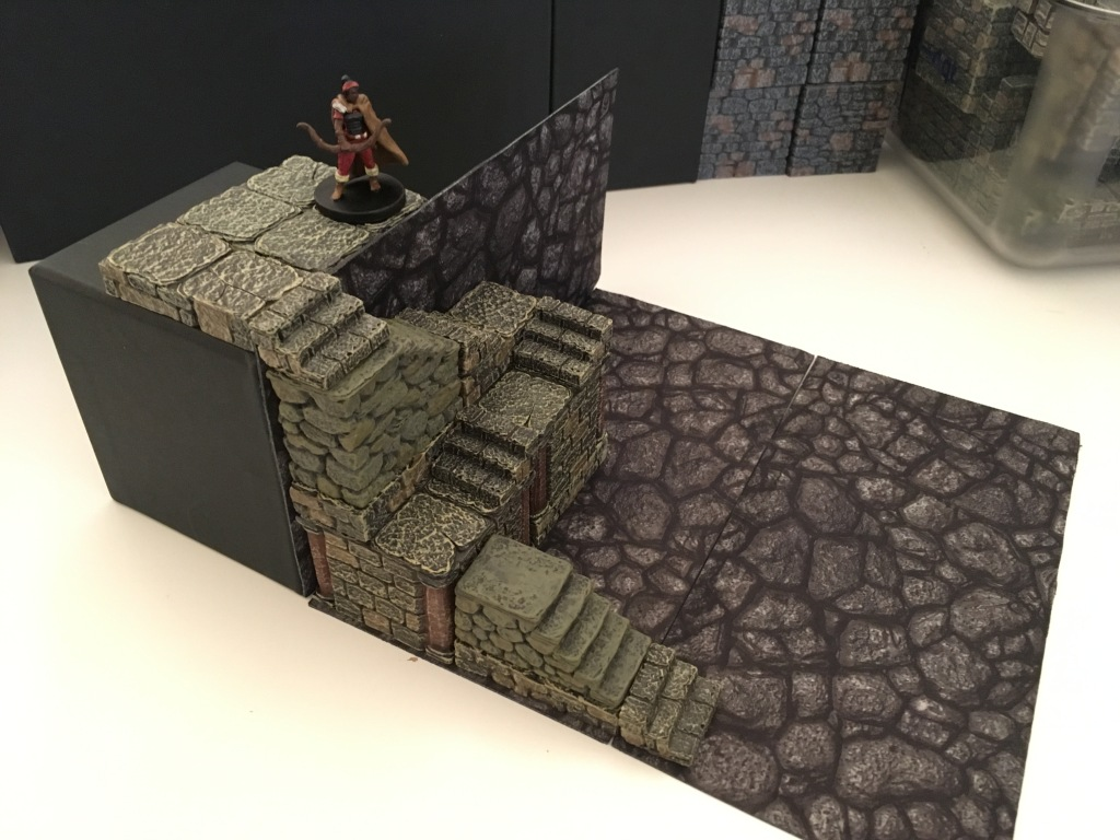 An archer watches over a winding staircase below her. The high structure she is on is the inverted medium square Tjena with a layer of floor tiles on top. The small terrain tray on its side comes up just below the top of that floor tile.