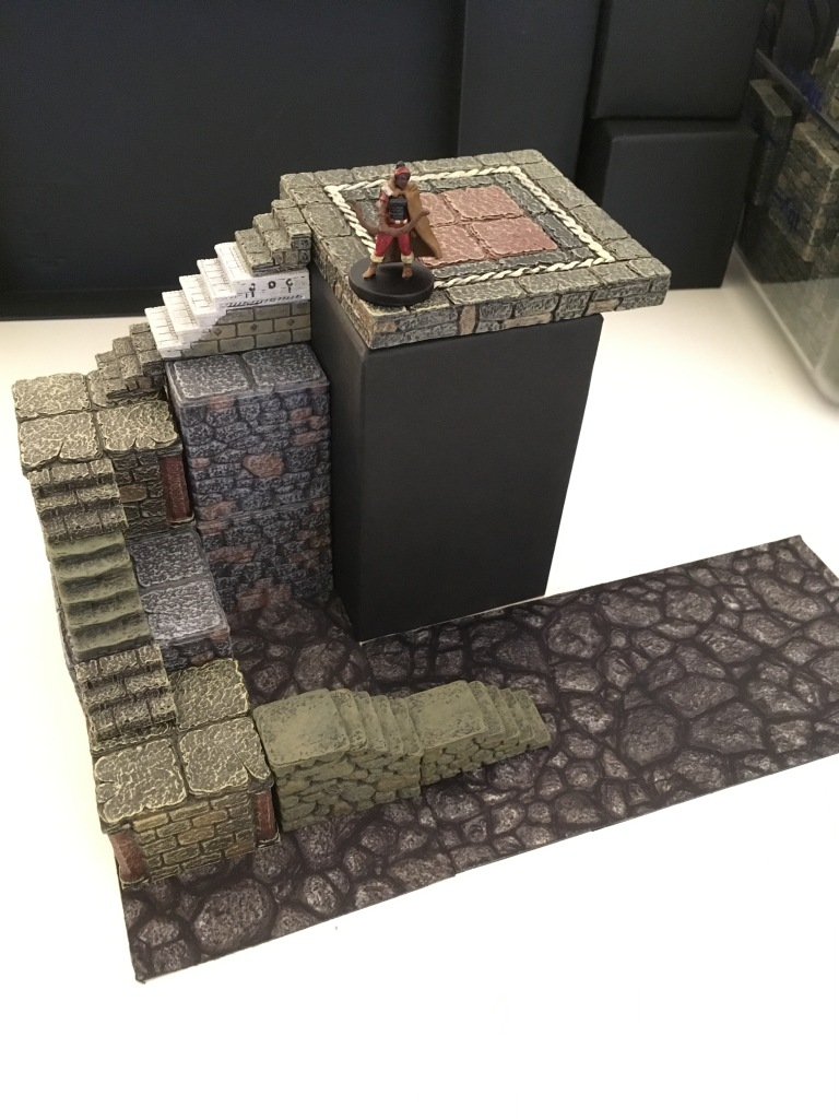 An archer watches over an even taller winding staircase below her. Again, a Tjena piece with a layer of floor tile provides the vantage point of the archer. It is the height of two elevation blocks, a 1x2 stair, and a stairjack. The black side of the box is fully visible but looks fine surrounded by the stone terrain and terrain tray below.