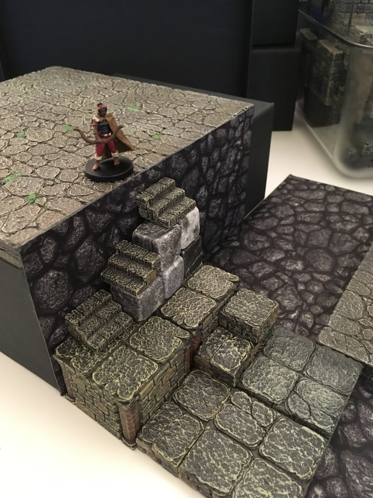 The archer guards a shorter staircase this time, but I bet she'll still skewer anyone who tries to get to her up the jumbled stone stairs. The big Tjena in its horizontal position with two  layers of floor tile on top is the same height as a small terrain tray on its side.