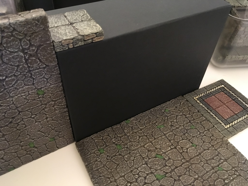 Dwarven Forge floor pieces are used next to the box to indicate its size for game purposes. It does not fit exactly to the grid.