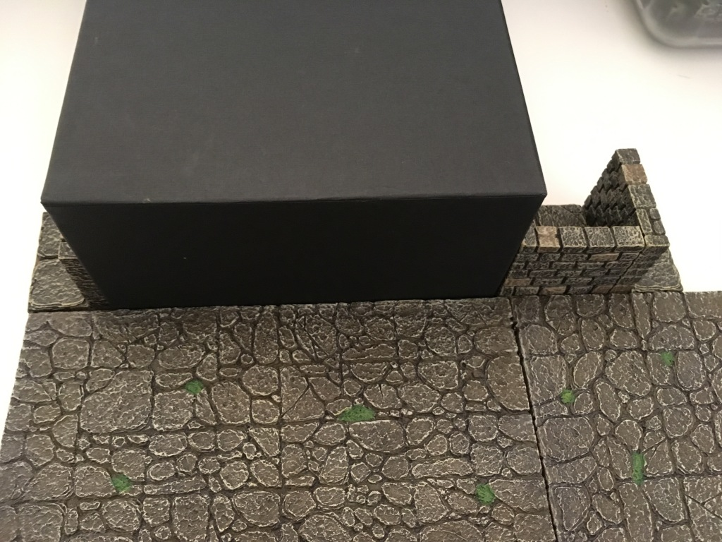 Dwarven Forge floor pieces are used next to the box to indicate its size for game purposes. It does not match the grid but through the use of a passage wall butted against it so that the floor of the wall is on the grid, it's fine.