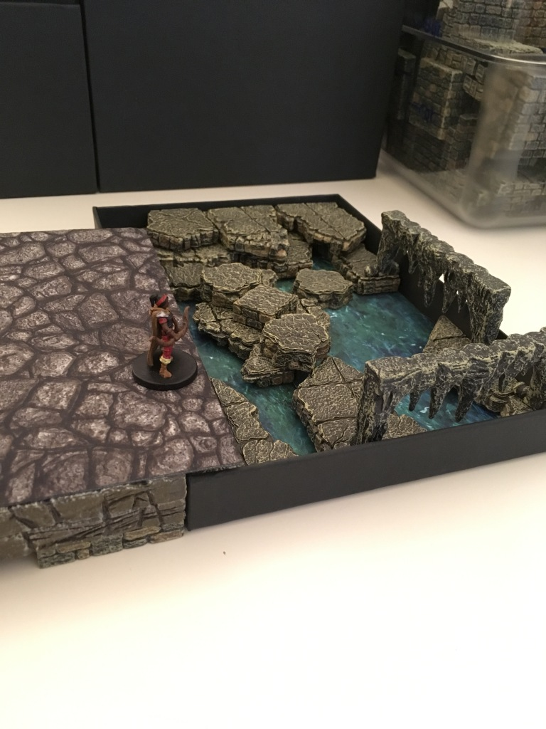 An adventurer stands overlooking a sunken area where the floors have collapsed to reveal water below flowing into caves The pit is the tray rightside up, with a smallwater terrain tray resting inside and cavern and cave pieces creating a jumbled flooded scene.