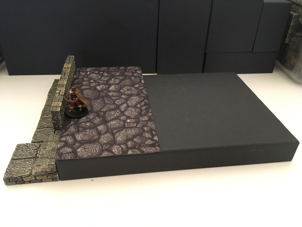 An archer stands behind a wall providing partial cover, guarding a short set of stairs. The wall is a normal dungeon wall pressed against the side of the upside down tray from the Tjena set. The figure stands on a flat terrain tray with a stone pattern. The stairs are a 2x2 floor tile with the stair jacks resting on them by the side of the tray.