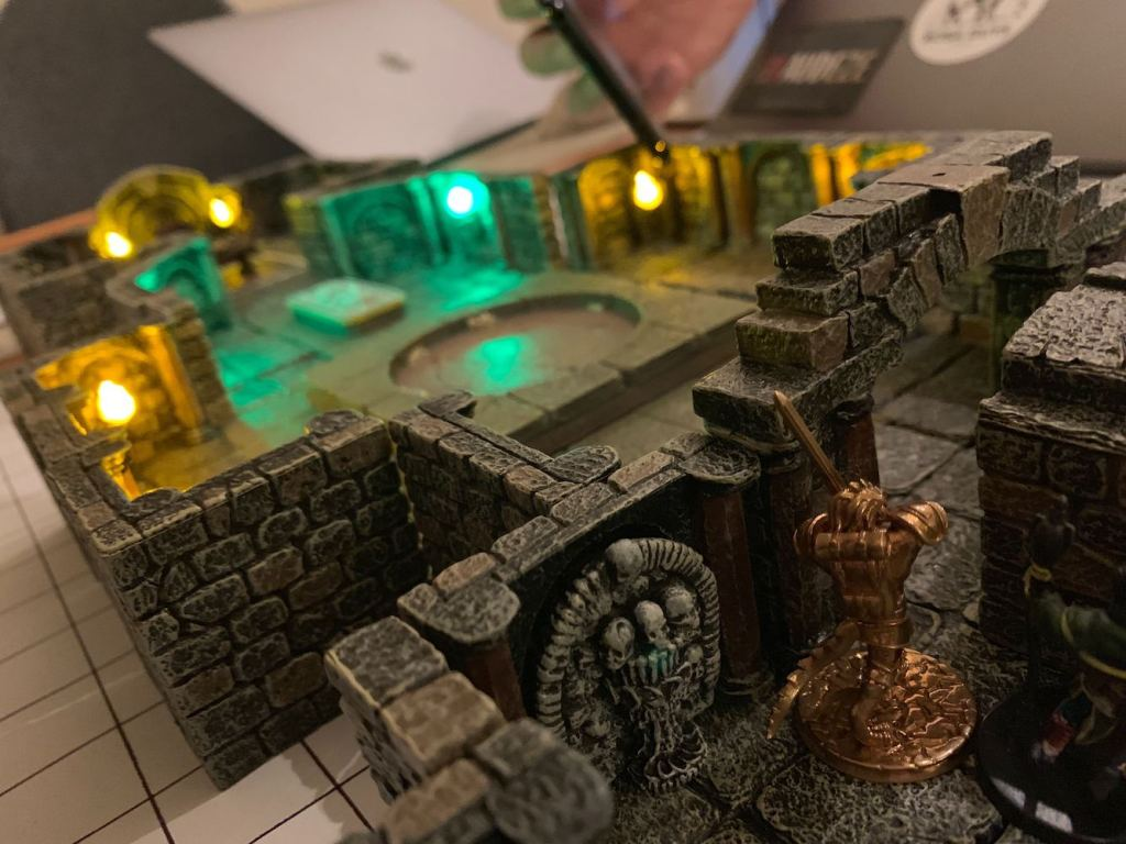 A photo taken low down near the table looking over the shoulder of a miniature of a dragonborn paladin wielding a sword as he prepares to enter an eerily lit stone tomb. In the background can be seen another player getting in low with their camera to take a picture.