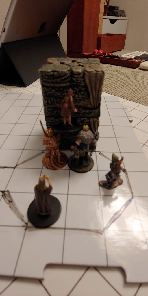 "A dry-erase mat with a 1"" grid has a small room drawn on it and a group of miniatures standing in the space. One edge has two blocks which look like rough cave stone stacked to be about two and a half times the height of the miniatures. One mini is balanced on the shoulders of two others and it is clear that they would not be able to reach the lip of the raised column unless the ones supporting her hoisted her higher, lifting her up from under her feet."