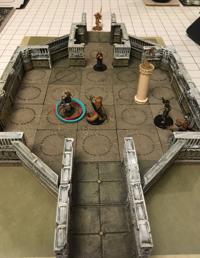 a rectangular terrain tray holds a large room with hallways in and out where a battle is taking place between involving some lizard/snake people, three more humanlike folk, and a shining dragonborn. A bird flies over the fracas.