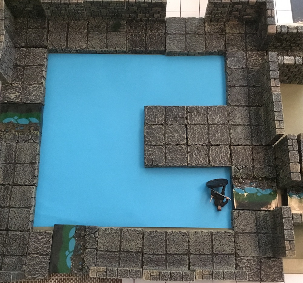 Plain bright blue paper under Dwarven Forge terrain, with a mini figure laying down on it near one side of the blue area.