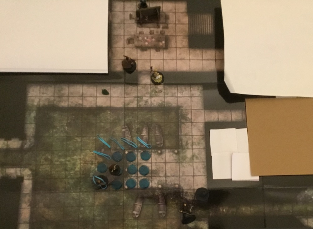 A Paizo flip mat with some unexplored parts covered by sticky notes and paper. The rubber bands and tokens and the mini figures representing the party and their foes sit atop it.