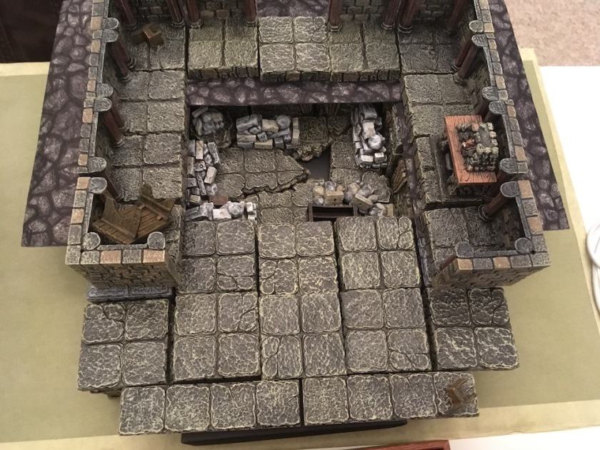 a terrain tray holds a house interior with a fireplace has clearly suffered some sort of disaster with furniture blown into the corners and the entire floor collapsed into a rubble filled basement