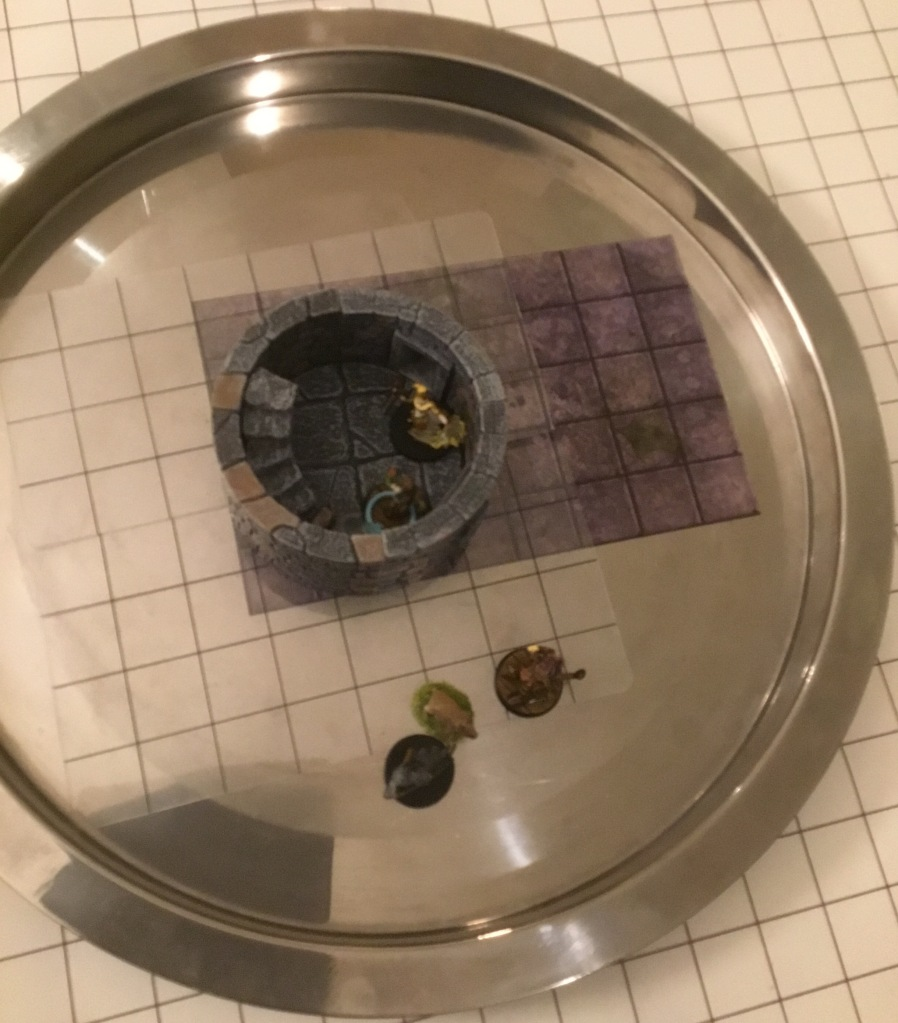 "A round metal tray with a raised rim has its surface partly covered with grid patterns held in place by a 4"" Dwarven Forge tower section."